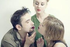 Deux femmes et un homme avec les cerises mûres rouges Photo stock
