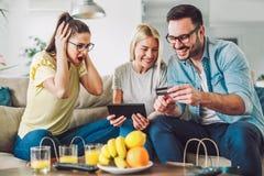 Deux femmes et un homme dans le salon tenant la carte de crédit Photos stock