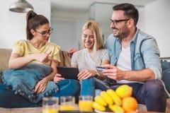 Deux femmes et un homme dans le salon tenant la carte de crédit Image libre de droits
