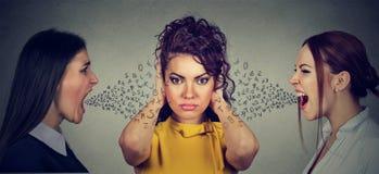 Deux femmes fâchées criant aux oreilles de bâche de fille les ignorant Photographie stock libre de droits