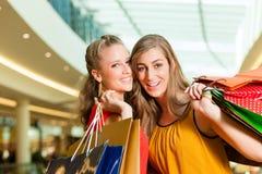 Deux femmes faisant des emplettes avec des sacs dans le mail Photographie stock libre de droits