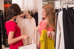 Deux femmes faisant des emplettes choisissant des robes Images stock