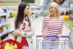 Deux femmes faisant des emplettes dans le supermarché Images stock