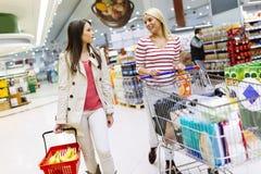 Deux femmes faisant des emplettes dans le supermarché Image stock