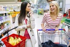 Deux femmes faisant des emplettes dans le supermarché Photographie stock libre de droits