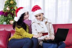 Deux femmes faisant des emplettes en ligne avec un ordinateur portable Images stock