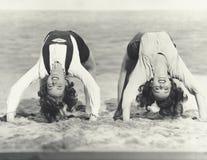 Deux femmes faisant des saltos sur la plage Image stock