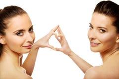 Deux femmes faisant le coeur avec des doigts Photographie stock