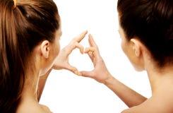 Deux femmes faisant le coeur avec des doigts Images stock