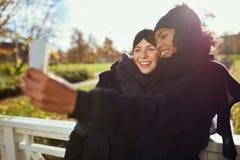 Deux femmes faisant le selfie en parc Image libre de droits