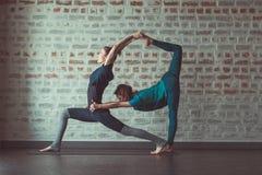 Deux femmes faisant le yoga d'associé dans le studio de yoga vis-à-vis du mur de briques images libres de droits