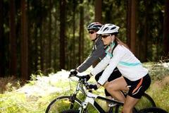 Deux femmes faisant un cycle dans la forêt Photos stock
