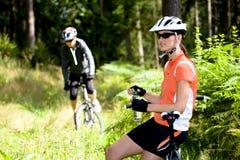 Deux femmes faisant un cycle dans la forêt Photos libres de droits