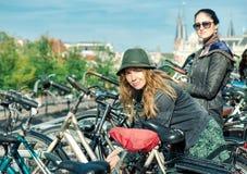 Deux femmes fermant à clef des vélos à Amsterdam Images libres de droits
