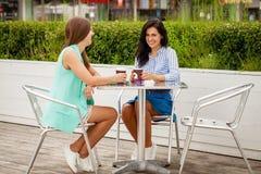 Deux femmes gaies de brune reposant le café d'été photographie stock