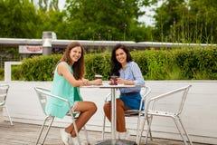 Deux femmes gaies de brune reposant le café d'été images libres de droits