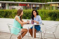 Deux femmes gaies de brune reposant le café d'été images stock