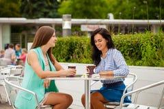 Deux femmes gaies de brune reposant le café d'été photo libre de droits
