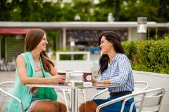 Deux femmes gaies de brune reposant le café d'été image stock