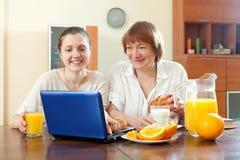 Deux femmes heureuses à l'aide de l'ordinateur portable pendant le petit déjeuner Photographie stock libre de droits