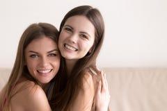 Deux femmes heureuses étreignant et regardant in camera Photographie stock