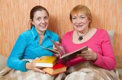 Deux femmes heureuses affichant un livre sur le sofa Photo stock