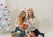 Deux femmes heureuses avec des boîte-cadeau ouvrent l'un d'entre eux Photo stock