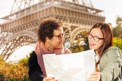 Deux femmes heureuses avec une carte de touristes de papier à Paris Photo stock