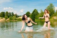 Deux femmes heureuses ayant l'amusement au lac en été Image libre de droits