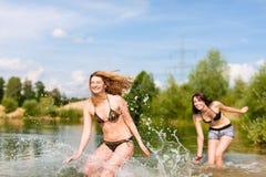 Deux femmes heureuses ayant l'amusement au lac en été Image stock