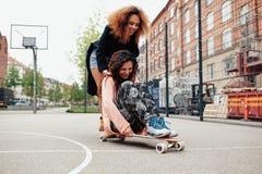 Deux femmes heureuses ayant le patinage d'amusement Photographie stock