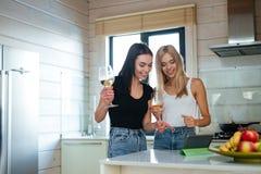 Deux femmes heureuses buvant du vin et à l'aide de la tablette Photo libre de droits