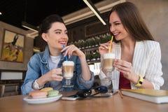 Deux femmes heureuses buvant la crème de latte Photo stock