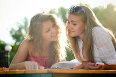 Deux femmes heureuses contrôlant la carte en café Photographie stock libre de droits