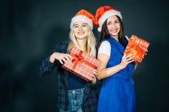 Deux femmes heureuses dans des chapeaux de Santa avec la position de boîte-cadeau Image libre de droits