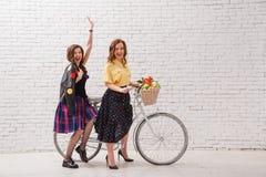 Deux femmes heureuses dans des robes d'été montent ensemble sur un rétro vélo et des mains de geste en avant Image stock