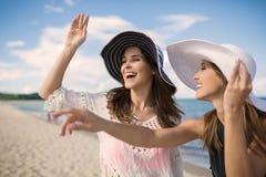 Deux femmes heureuses dans le chapeau riant sur la plage Photo libre de droits