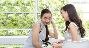 Deux femmes heureuses de dame à l'aide du comprimé se reposant dans le café Yo deux Images stock