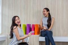 Deux femmes heureuses employant des achats sur le téléphone portable et le comprimé Achats de sourire de deux jeunes femmes Trava image stock