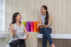 Deux femmes heureuses employant des achats sur le téléphone portable et le comprimé Achats de sourire de deux jeunes femmes Trava images libres de droits