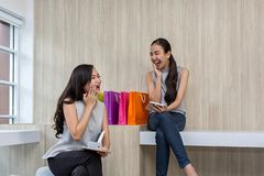 Deux femmes heureuses employant des achats sur le téléphone portable et le comprimé Achats de sourire de deux jeunes femmes Trava photo stock