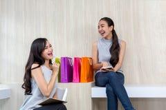 Deux femmes heureuses employant des achats sur le téléphone portable et le comprimé Deux y photographie stock