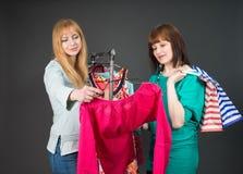 Deux femmes heureuses faisant des emplettes dans la mémoire de vêtements Photographie stock