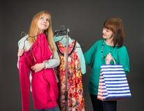 Deux femmes heureuses faisant des emplettes dans la mémoire de vêtements Images stock