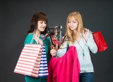Deux femmes heureuses faisant des emplettes dans la mémoire de vêtements Image libre de droits