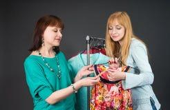 Deux femmes heureuses faisant des emplettes dans la mémoire de vêtements Image stock