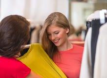 Deux femmes heureuses faisant des emplettes dans la mémoire de vêtements Photos libres de droits