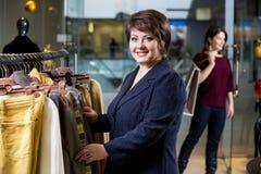 Deux femmes heureuses faisant des emplettes dans le magasin de vêtements Photographie stock