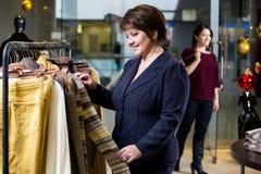 Deux femmes heureuses faisant des emplettes dans le magasin de vêtements Photographie stock libre de droits