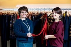 Deux femmes heureuses faisant des emplettes dans le magasin de vêtements Photos stock